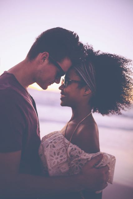 Loving mixed race couple on a beach at sunset. No need for sex therapy.